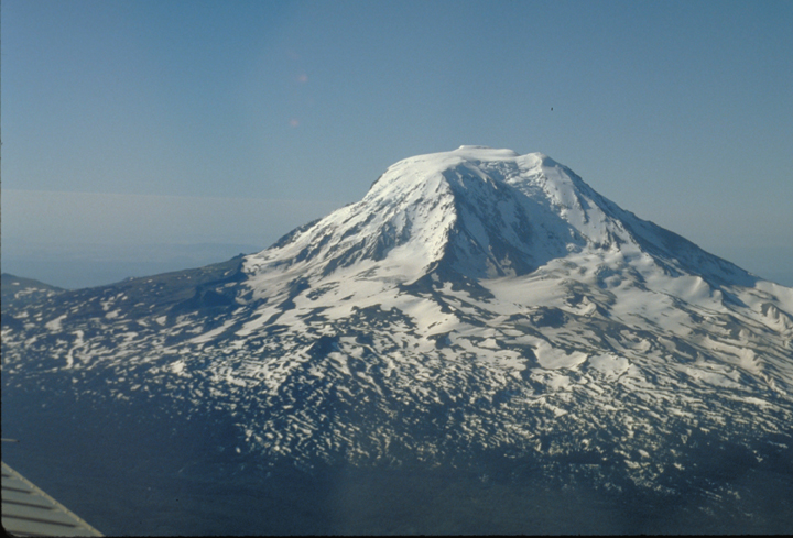 This aerial shows the mountain dominating the image, its square top still covered with snow.